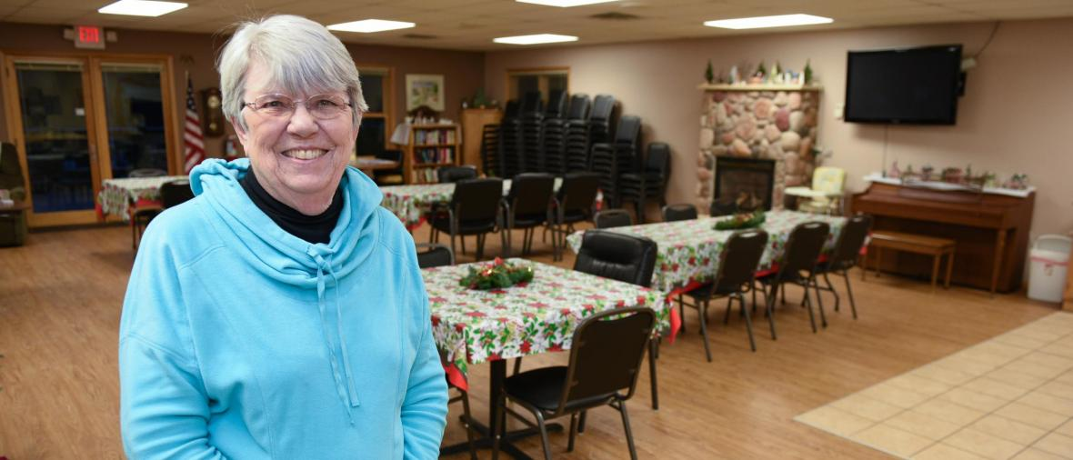 An older woman smiles in front of a new dining room