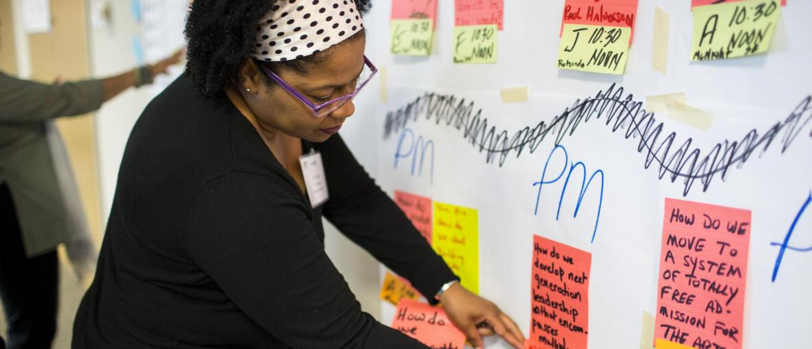 Woman placing post-it note on board