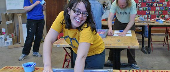 a woman is screen printing shirts