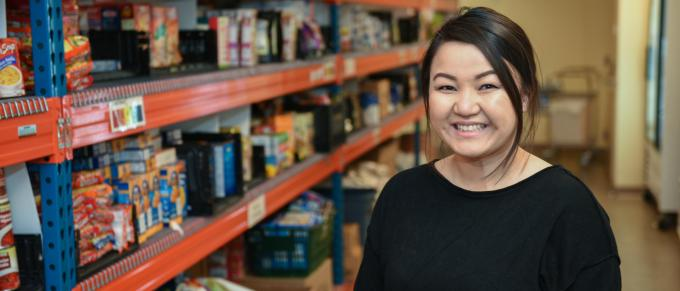 a woman stands in front of a food shelf