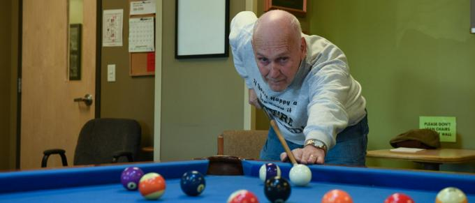 an older man plays pool