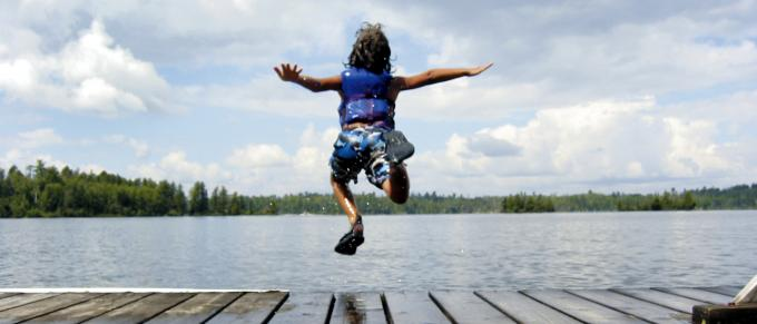Boy jumping into a lake